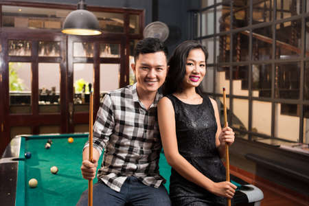 pool cues: Young Asian couple holding cues sitting on the edge of the pool table