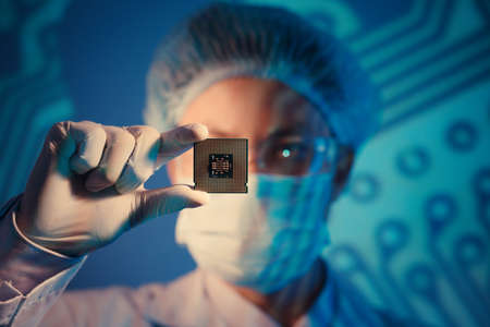 Computer engineer holding microchip for detailed analysis on the foreground