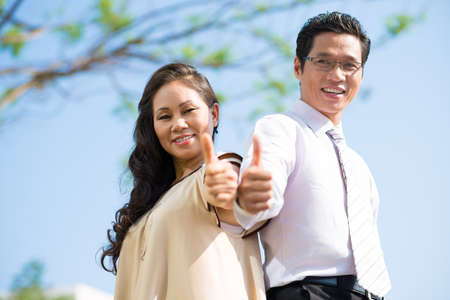 Angle view of businesspeople thumbing up in the sign of self-respect on the foreground Stock Photo
