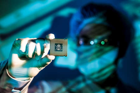 Cropped image of an engineer holding computer microchip on the foreground Imagens