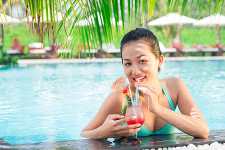 Copy-spaced portrait of a young woman in swimwear drinking tropical cocktail in the pool