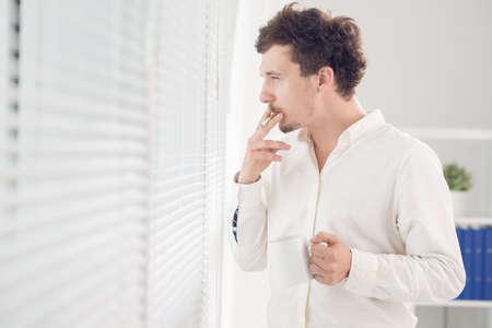 Smoking man looking through jalousie