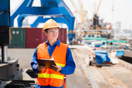 superintendent: Copy-spaced image of a port superintendent with clipboard controlling the working process in the seaport Stock Photo