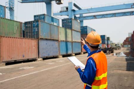 Achteraanzicht van een zeehaven inspecteur bezig met in-checking Stockfoto