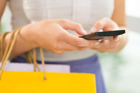 Cropped image of female hands carrying bags and dialing a telephone number on the foreground Stock Photo