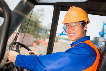 safety googles: Closeup portrait of a smiling longshoreman looking at camera white driving a working machine Stock Photo