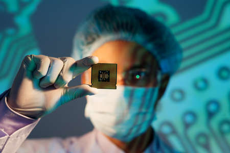 Image of an electronic engineer analyzing computer microchip holding on the foreground