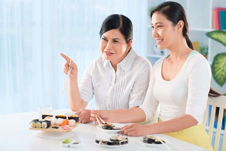 Portrait of young Asian woman and her mother talking while eating sushi in the kitchen Stock Photo