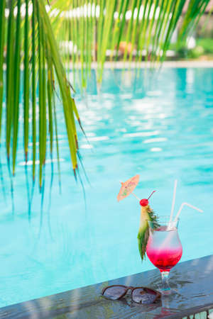 chilled out: Vertical image of a glass of tasty tropical cocktail on the pool Stock Photo