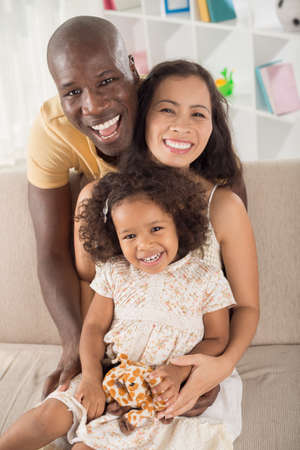 Vertical portrait of a mixed cheerful family posing at camera