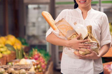 Cropped image of a woman standing with basic food in hands