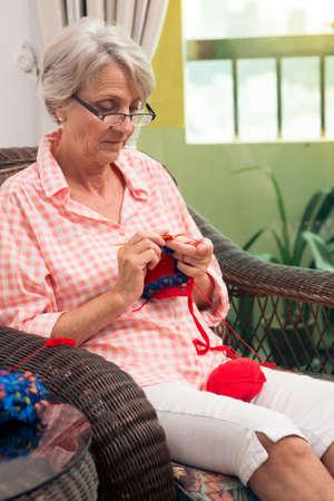 Mature woman knitting in an armchair Stock fotó