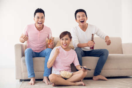 Group of friends watching sport game on tv