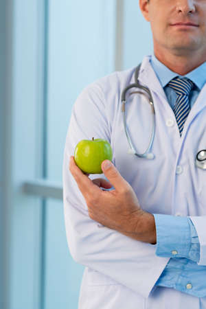 md: Close-up of doctor holding green apple Stock Photo