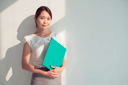 asian businesswoman: Portrait of Asian businesswoman with a green folder