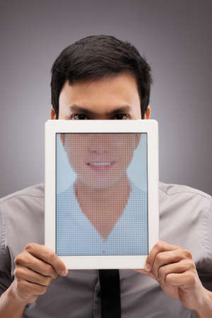 serious guy: Portrait of serious man with half of his face covered by a digital tablet with an image of smiling guy