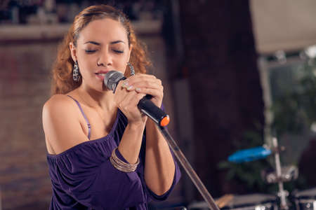 Latin brunette singing with a microphone