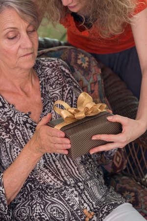 Old woman receiving a present from her granddaughter