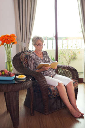 Old lady sitting and reading in an armchair indoors