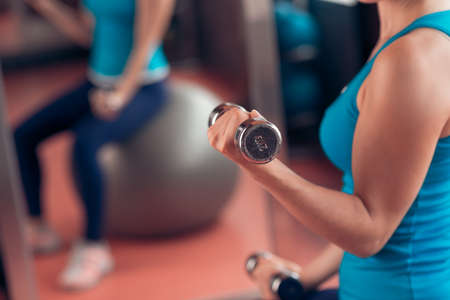 lift hands: Woman lifting dumbbells in the gym Stock Photo