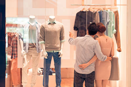 Man showing clothes in the shop window to his girlfriend, rear view Stock Photo - 72845331