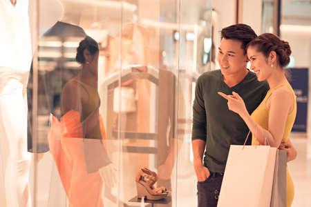 若い女性が彼女の夫に何か店の窓で表示