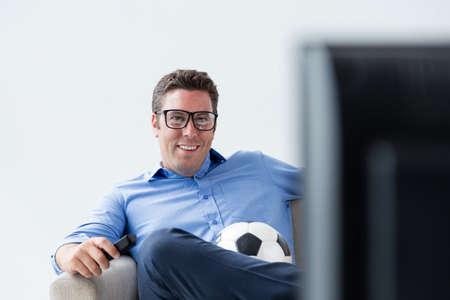 Smiling man watching tv at home Stock Photo