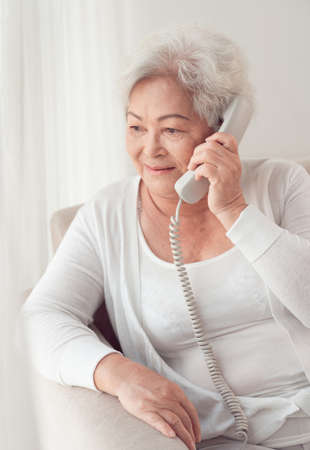 Aged Asian woman talking on the phone