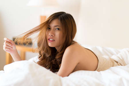 Portrait of attractive Vietnamese woman playing with her hair, while lying in bed Stock Photo