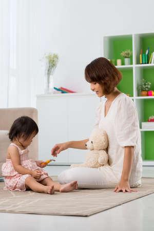 Moeder en dochter die op de vloer thuis spelen Stockfoto