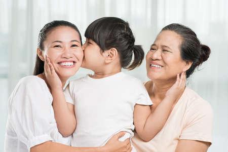 Petite fille embrasse sa mère et lie sa grand-mère
