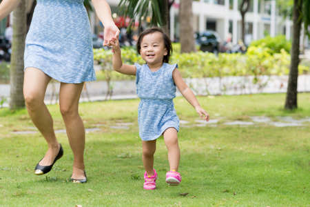 Little Asian girl running with her mother in the park