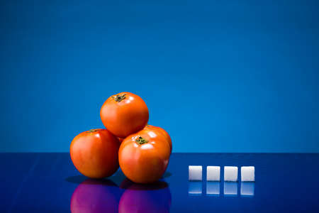 Still life showing amount of sugar in four tomatoes