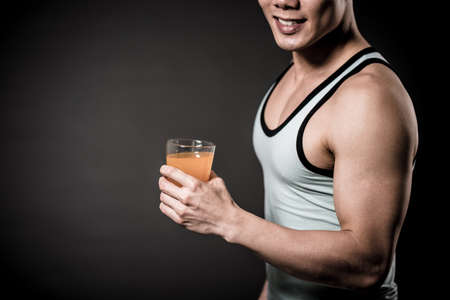 Muscular man holding a glass of orange juice Stock Photo