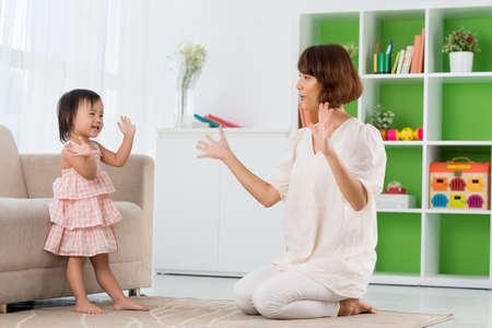 중국 어머니와 딸이 박수 치는 경기를하고있다.