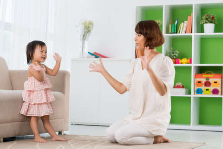 Chinese mother and daughter playing clapping game Stock Photo