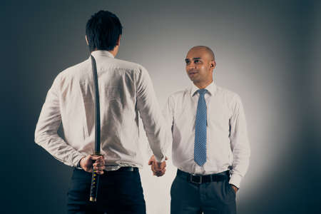 Businessman shaking hands with his partner while hiding katana sword behind his back