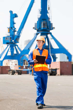 Inspector walking round cargo port Stock Photo
