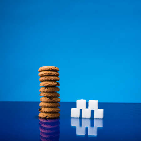 Still life showing amount of sugar in a stack of chocolate chip cookies Stock Photo