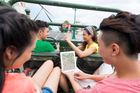 Dziewczyna robi zdjęcie kierowcy samochodu, podczas gdy jej przyjaciele na tylnym siedzeniu korzystają z tabletu z nawigatorem na ekranie Zdjęcie Seryjne