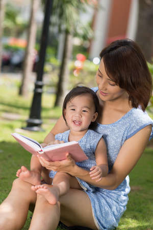 Chinese little girl and her mother reading a book in the park