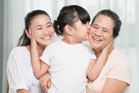 Small  girl kissing her grandmother and bonding her mother