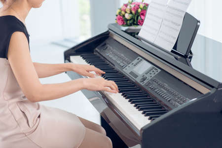 natation: Side view of woman playing piano, body and buttons of the piano were digitally modified