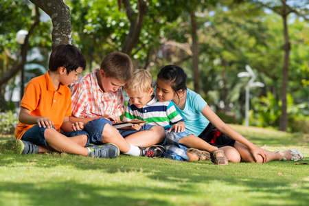 Group of children using digital tablet in the park