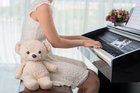 Unrecognizable girl playing piano when her teddy bear is sitting by her