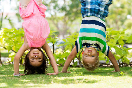 Two playful children standing on their hands in the park Stock Photo
