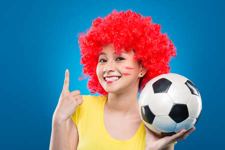 Portrait of female soccer fan showing the amount of goals with her finger