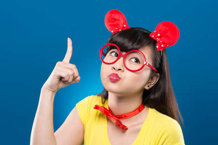 Young girl in red framed glasses pointing up with her finger