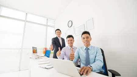 happy asian people: Business team showing thumbs up as a symbol of success
