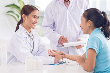 Female intern measuring the pulse of the patient while doctor writing down the results Stock Photo